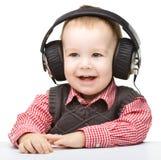 Rapaz pequeno bonito que aprecia a música usando auscultadores Imagem de Stock Royalty Free