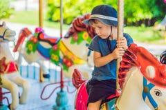 Rapaz pequeno bonito que aprecia no funfair e que monta no carou colorido Imagens de Stock