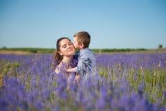 Rapaz pequeno bonito que beija sua mãe bonita com seus olhos fechados com prazer Imagens de Stock