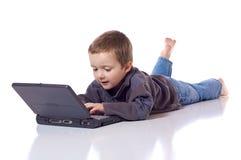 Menino bonito com um portátil Fotografia de Stock