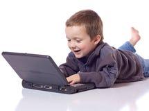 Menino bonito com um portátil Fotos de Stock
