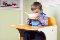 Rapaz pequeno bonito que come de uma bacia Imagem de Stock Royalty Free