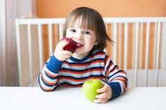 Rapaz pequeno bonito que come maçãs Fotografia de Stock
