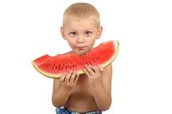 Rapaz pequeno bonito que come a melancia Imagem de Stock