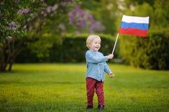 Rapaz pequeno bonito que guarda a bandeira do russo durante o passeio no parque do verão foto de stock royalty free