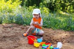 Rapaz pequeno bonito que joga com a areia no campo de jogos Fotos de Stock