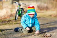 Rapaz pequeno bonito que joga com as varas de madeira no parque da cidade, exterior Imagens de Stock Royalty Free