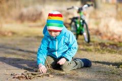 Rapaz pequeno bonito que joga com as varas de madeira no parque da cidade, exterior Fotografia de Stock Royalty Free