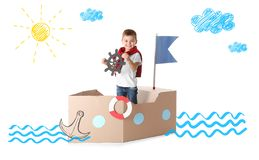 Rapaz pequeno bonito que joga com navio do cartão fotos de stock
