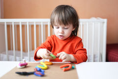 Rapaz pequeno bonito que joga com plasticine em casa Fotografia de Stock