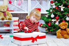 Rapaz pequeno bonito que joga com seu carro vermelho do brinquedo Imagem de Stock