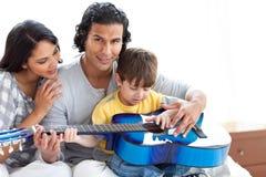 Rapaz pequeno bonito que joga a guitarra com seus pais Fotos de Stock Royalty Free