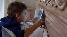 Rapaz pequeno bonito que joga nos jogos de tablet pc vídeos de arquivo