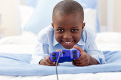 Rapaz pequeno bonito que joga o jogo video Fotografia de Stock Royalty Free