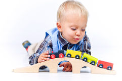 Rapaz pequeno bonito que joga trens Fotos de Stock