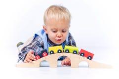 Rapaz pequeno bonito que joga trens Fotografia de Stock Royalty Free