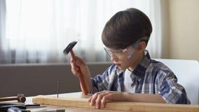 Rapaz pequeno bonito que martela o prego no tempo de madeira da prancha, do passatempo e de lazer, oficina video estoque