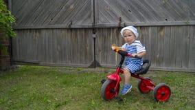 Rapaz pequeno bonito que monta uma bicicleta vermelha na jarda imagens de stock royalty free