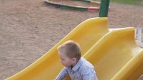 Rapaz pequeno bonito que move-se para baixo da corrediça do ` s das crianças no parque vídeos de arquivo
