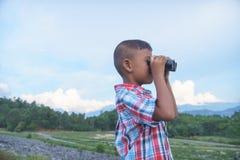 Rapaz pequeno bonito que olha com binocular imagens de stock royalty free