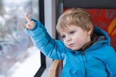 Rapaz pequeno bonito que olha para fora o indicador do trem Fotos de Stock Royalty Free