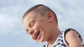 Rapaz pequeno bonito que ri e que sorri no fundo do céu filme