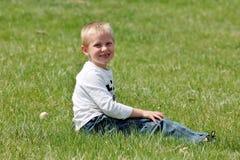 Rapaz pequeno bonito que senta-se na grama Imagens de Stock