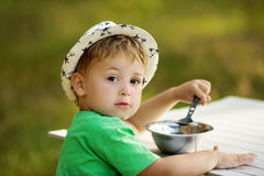 Rapaz pequeno bonito que senta-se na tabela e que come no campo Imagem de Stock