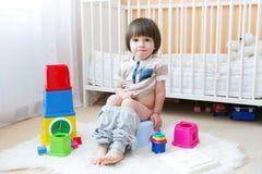 Rapaz pequeno bonito que senta-se no urinol em casa Imagem de Stock