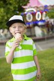Rapaz pequeno bonito que sorri e que lambe seu gelado em um carnaval exterior Foto de Stock