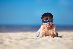 Rapaz pequeno bonito que tem o divertimento na praia Fotografia de Stock