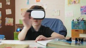Rapaz pequeno bonito que tem uma conversação video do bate-papo usando auriculares da realidade virtual filme