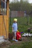Rapaz pequeno bonito que trabalha no jardim Imagem de Stock