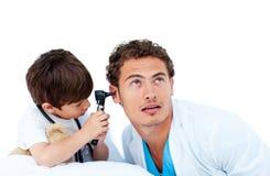 Rapaz pequeno bonito que verific as orelhas do doutor Fotografia de Stock Royalty Free