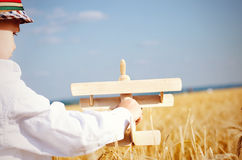 Rapaz pequeno bonito que voa um plano do brinquedo em um wheatfield Imagens de Stock Royalty Free