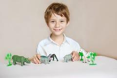 Rapaz pequeno bonito, sorrindo na câmera, animais em torno dele, tiro interno imagens de stock