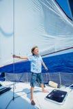 Rapaz pequeno a bordo do iate da navigação no cruzeiro do verão Aventura do curso, vela com a criança em férias em família imagens de stock