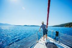 Rapaz pequeno a bordo do iate da navigação no cruzeiro do verão Aventura do curso, vela com a criança em férias em família Imagem de Stock Royalty Free