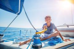 Rapaz pequeno a bordo do iate da navigação no cruzeiro do verão Aventura do curso, vela com a criança em férias em família fotos de stock royalty free