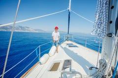 Rapaz pequeno a bordo do iate da naviga??o no cruzeiro do ver?o Aventura do curso, vela com a crian?a em f?rias em fam?lia imagem de stock royalty free