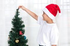 Rapaz pequeno chinês asiático que decora a árvore de Natal em casa Imagem de Stock Royalty Free