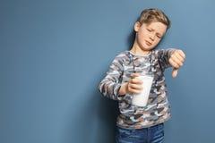 Rapaz pequeno com a alergia da leiteria que guarda o vidro do leite fotografia de stock