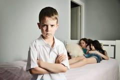 Rapaz pequeno com as testas sulcadas no primeiro plano no whi da sala Fotos de Stock Royalty Free