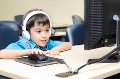 Rapaz pequeno com auriculares usando o computador na sala de aula foto de stock