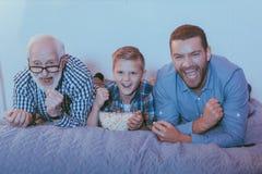 Rapaz pequeno com a bacia de pipoca, de seu pai e de avô na cama, olhando um filme fotos de stock royalty free