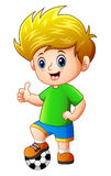 Rapaz pequeno com a bola de futebol que dá os polegares acima Imagem de Stock