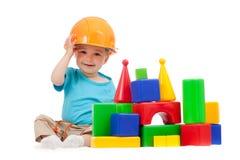 Rapaz pequeno com chapéu duro e blocos de apartamentos imagem de stock