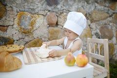 Rapaz pequeno com cozimento do chapéu do cozinheiro chefe Imagem de Stock