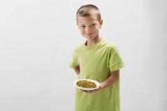 Rapaz pequeno com ervilhas fotografia de stock royalty free