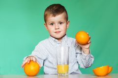 Rapaz pequeno com laranjas e suco imagem de stock